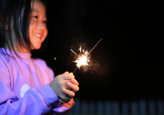 Little asian child girl enjoy playing firecrackers Premium Photo