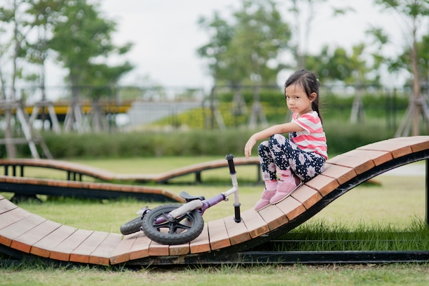Little asian child girl fallen from bike at playground Premium Photo