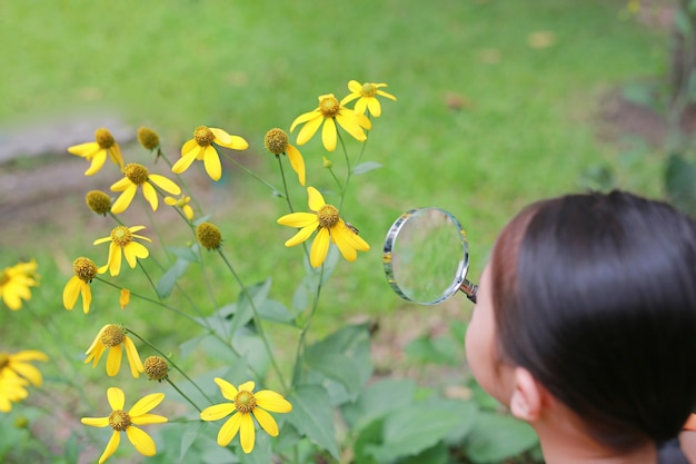 Little asian child girl with magnifying glass on green grass garden. Premium Photo
