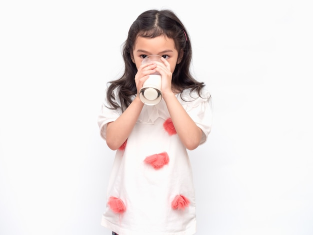 Little asian cute girl 6 years old holding and drinking milk from glasses Premium Photo
