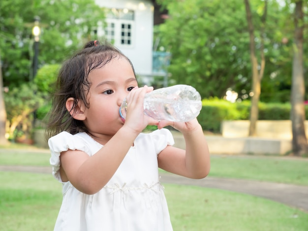 Little Asian Cute Girl Drinking Water From Plastic Bottle After