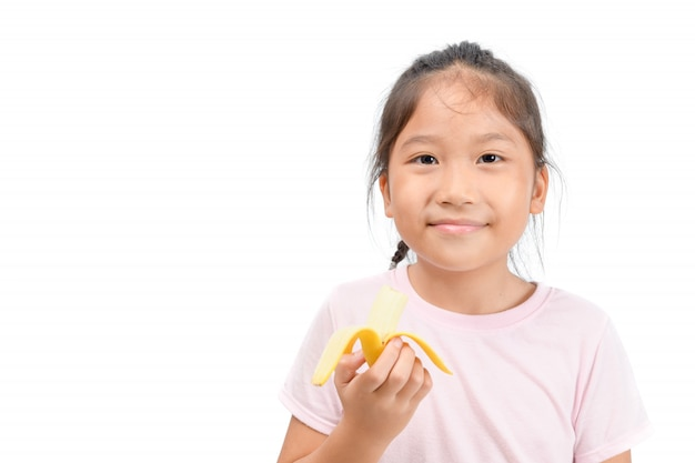 Little asian cute girl eats banana isolated on white Premium Photo