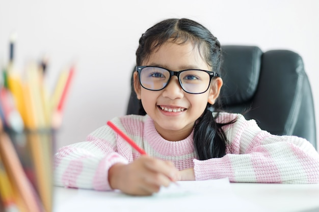 Little asian girl doing homework and smile with happiness for education concept select focus shallow depth of field Premium Photo