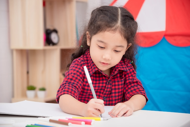 Little asian girl drawing picture by color marker on table at home Premium Photo