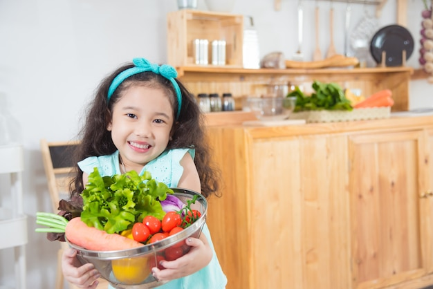 Little asian girl holding basket with many vegetables and smiles in kitchen Premium Photo