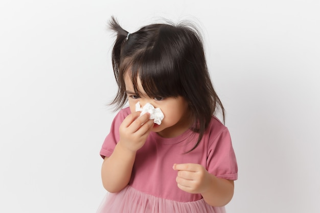 Little asian girl holding a tissue and blow her nose. kid with ...