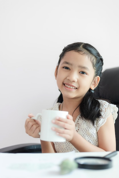 Little asian girl holding white mug and smile with happiness select focus shallow depth of field Premium Photo