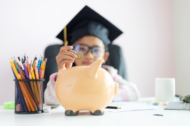 Little asian girl putting the coin into piggy bank and smile with happiness for money saving to wealthness in the future of education concept select focus shallow depth of field Premium Photo