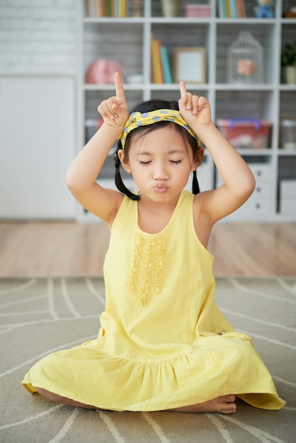 Little asian girl sitting on floor at home and making cow horns gesture Free Photo