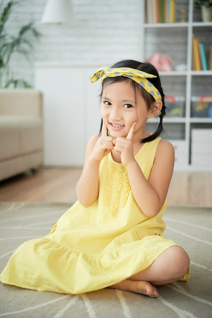 Little asian girl sitting on floor at home and posing with fingers on cheeks Free Photo