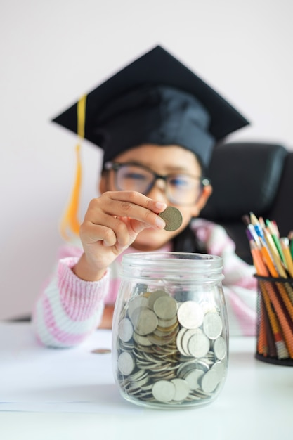 Little asian girl wearing graduate hat putting a coin into clear glass jar Premium Photo