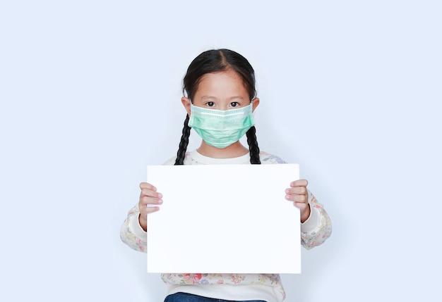 白い背景に空白の白い紙を表示して保護マスクを身に着けている小さなアジアの女の子。 Premium写真