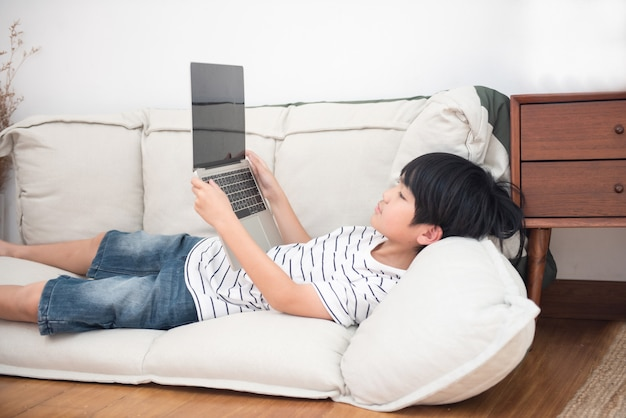 Little asian school boy in white shirt laying in his bed play on laptop. social network addiction concept. child pc dependence Premium Photo