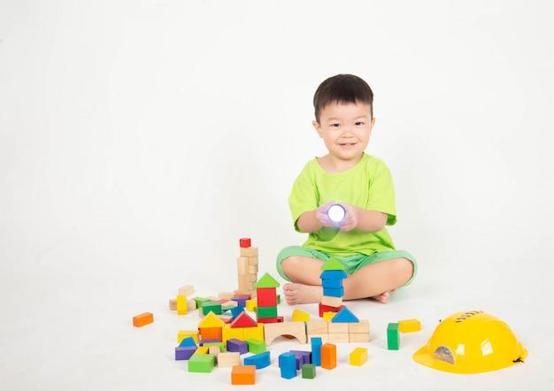 Little asian toddler boy playing wood blocks wear helmet engineer Premium Photo