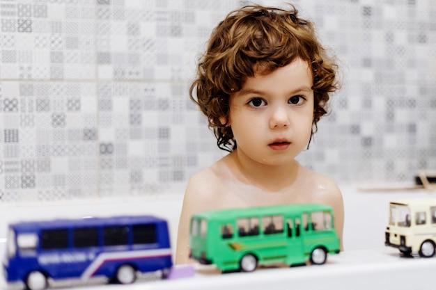 Маленький аутичный мальчик в ванной комнате играет с игрушечным автобусом Premium Фотографии