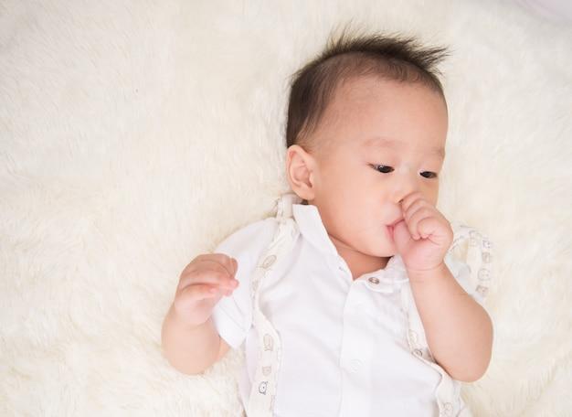 口の中に親指で7ヶ月の小さな男の子 Premium写真