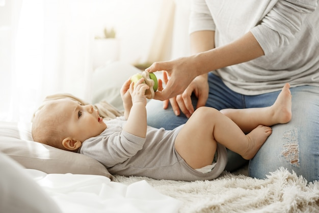Little baby boy spending happy childhood with young mother. child trying to take a beautiful toy from tender mom hands. family concept. Free Photo