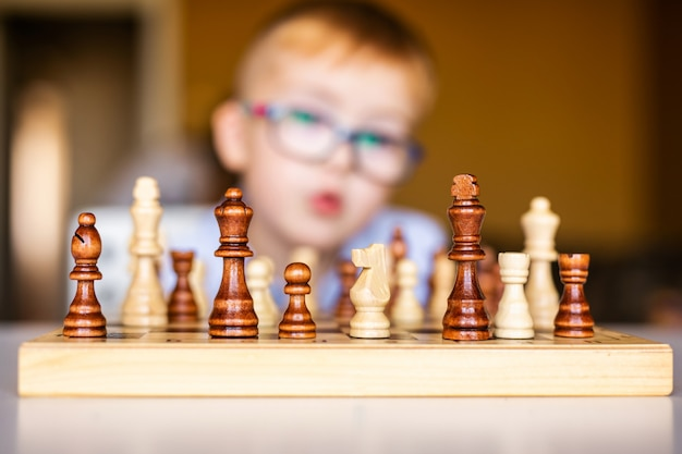 Little baby boy with down syndrome with big blue glasses playing chess in kindergarten Premium Photo