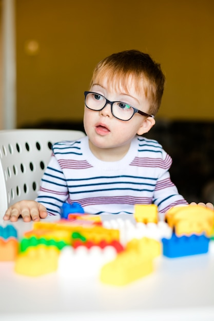 Little baby boy with down syndrome with big blue glasses playing with colorful bricks Premium Photo