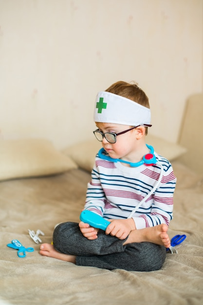 Little baby boy with down syndrome with big blue glasses playing with doctor toys Premium Photo