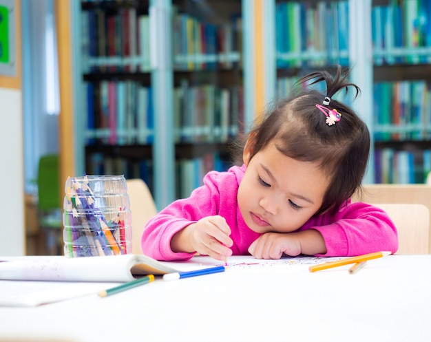 Little baby cute girl use colors pencil drawing at white paper at the library. Premium Photo