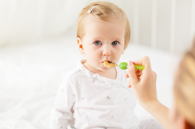 Little baby feeding with a spoon Premium Photo