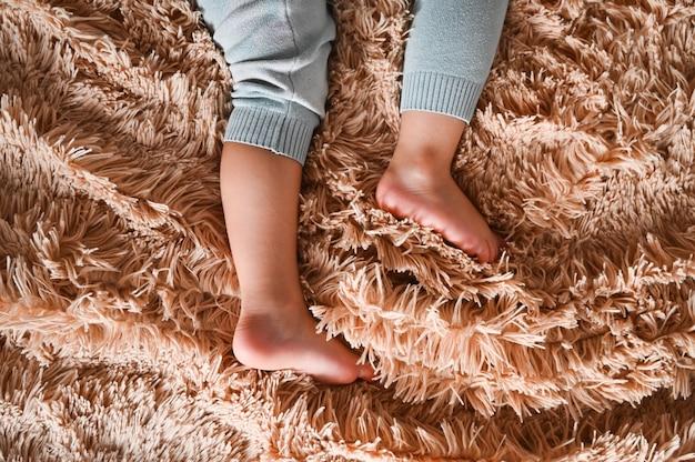 Ножки младенца на пушистой поверхности пледа. Premium Фотографии
