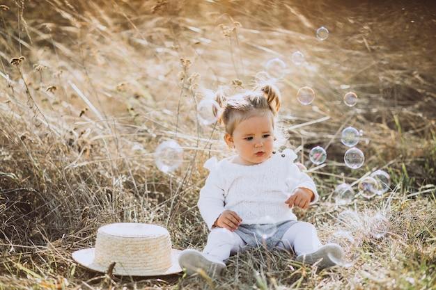 Little baby girl blowing soap bubbles in field Free Photo