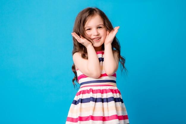 Little baby girl smiling on blue Premium Photo