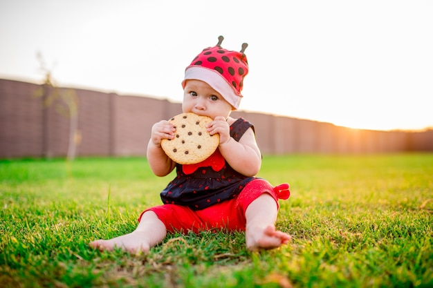 Little baby-girl with a large chocolate cookie sits on the back-yard Free Photo