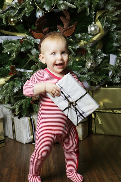 Маленькая девочка с подарочной коробке возле украшения елки Premium Фотографии