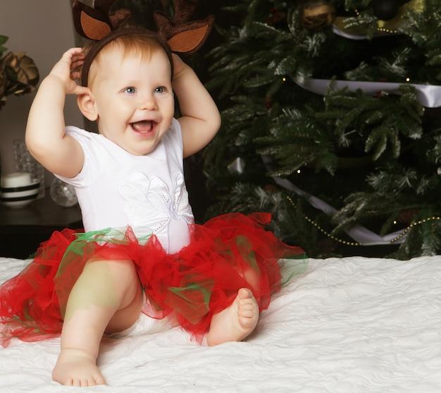 Маленькая девочка с подарочной коробкой возле украшения елки. Premium Фотографии