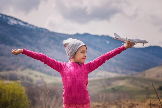 山と空を背景に白いおもちゃの飛行機を手に小さな女の赤ちゃん Premium写真