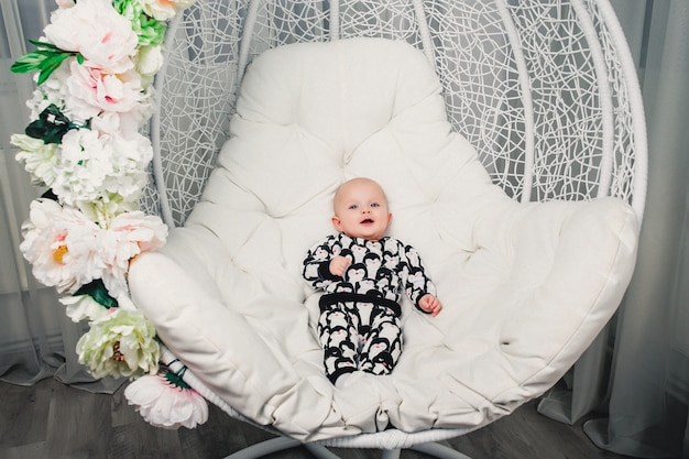 Little baby lying on a round swing and smiling Premium Photo