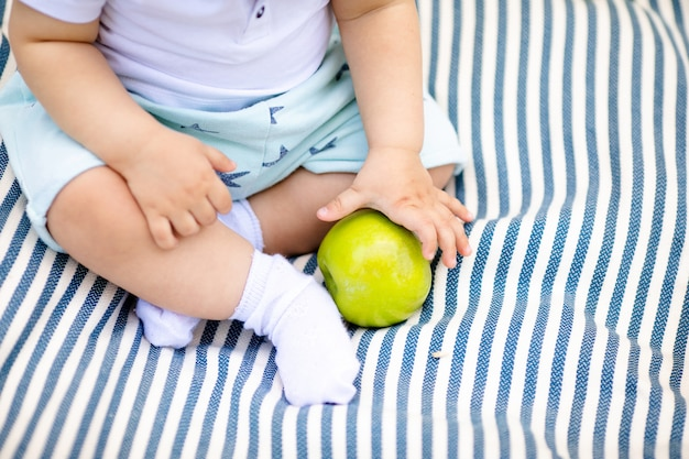 Little baby's fingers holding yellow pear Premium Photo
