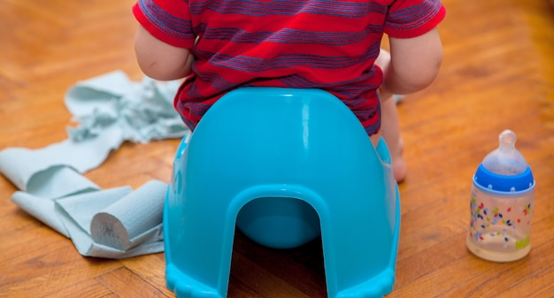 Little baby sitting on chamber pot with toilet paper and pacifier on a brown background Premium Photo