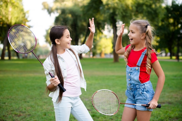 Little badminton players giving five Free Photo