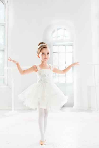 Маленькая балерина девушка в пачке. очаровательный ребенок танцует классический балет Бесплатные Фотографии