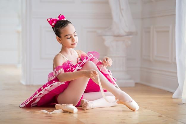 明るいピンクのチュチュを結ぶ靴の小さなバレリーナ Premium写真