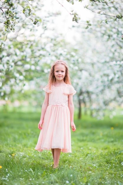 Little beautiful girl enjoying smell in a flowering spring garden Premium Photo