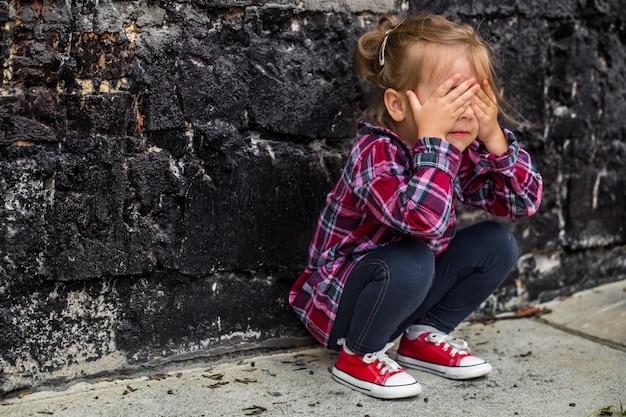 Little beautiful girl near brick wall Free Photo