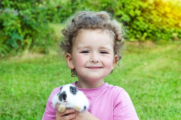 笑みを浮かべて、緑の芝生に赤ちゃんウサギを抱いて美しい少女。幸せな笑い子とペット Premium写真