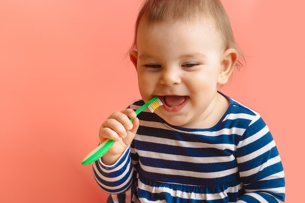 Little beautifulbaby toddler cleaning teeth with child brush on pink background Premium Photo