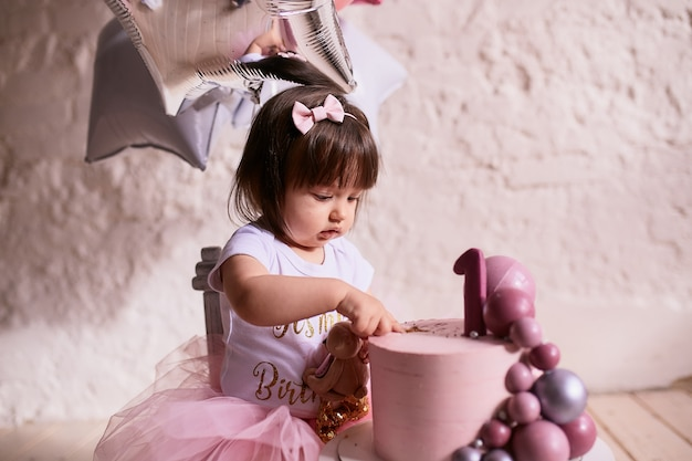 Little birthday girl. charming baby in pink dress sits on the chair Free Photo