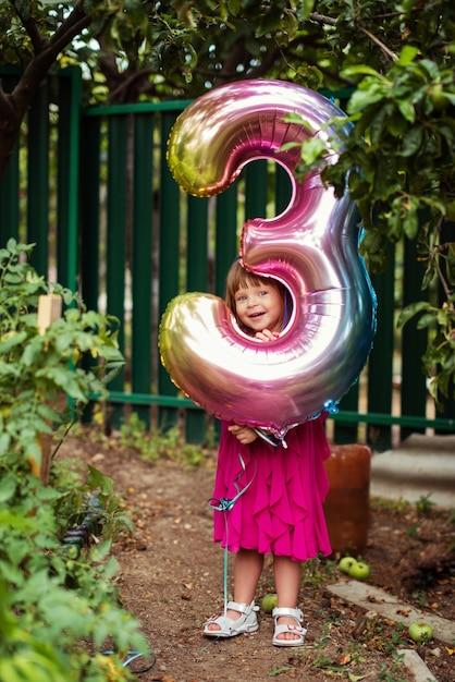 야외에서 세 가지 모양의 풍선과 함께 작은 생일 소녀 프리미엄 사진