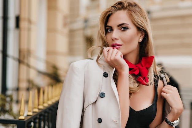Немного удивленная женщина-модель в куртке позирует возле дома утром Бесплатные Фотографии