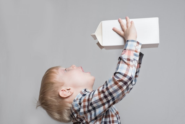 Little blond boy drinks from a large white package. Premium Photo