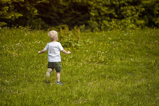 金髪の少年は、森の端にある緑の牧草地で実行されます。 Premium写真