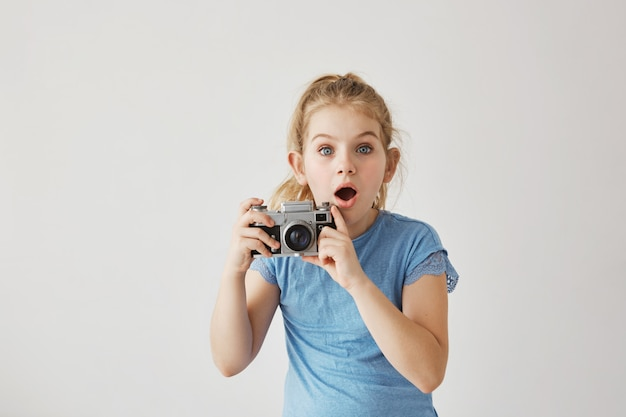 Little blond miss with blue eyes was taking family photo of parents with film camera when dad slipped and fell down. child looking frightened that parent get hurt. Free Photo
