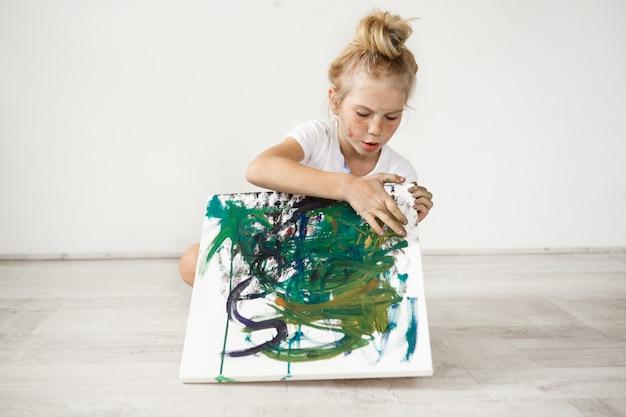 Bambina bionda con hairbn e lentiggini che indossa una maglietta bianca occupata con la sua foto. ragazza carina, adorabile, seduta su un pavimento con tela colorata in ginocchio. Foto Gratuite
